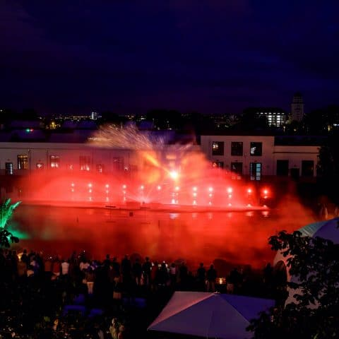 Epischer Moment: Die Wasserwand erstrahlt in einem rot