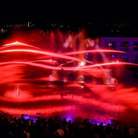 Rote Laserwellen auf der Wasserleinwand